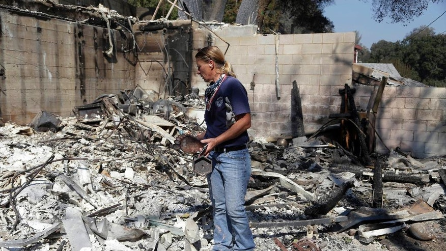 Karrie H. Andrews recovers items salvaged from the ruins of her home Tuesday, July 26, 2016, destroyed when the Sand fire swept through Santa Clarita, Calif. over the weekend. The fire destroyed 18 homes and authorities said that by Tuesday it had burned more than 37,000 acres, about 58 square miles. (AP Photo/Nick Ut)