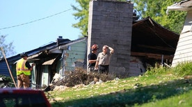 Law enforcement investigators in Omaha, Neb., look for clues Tuesday, July 26, 2016, at the scene of a house where an explosion took place on Monday, killing a woman, in Omaha. Authorities say the woman was a property inspector sent to check its condition after a tenant was evicted. (AP Photo/Nati Harnik)