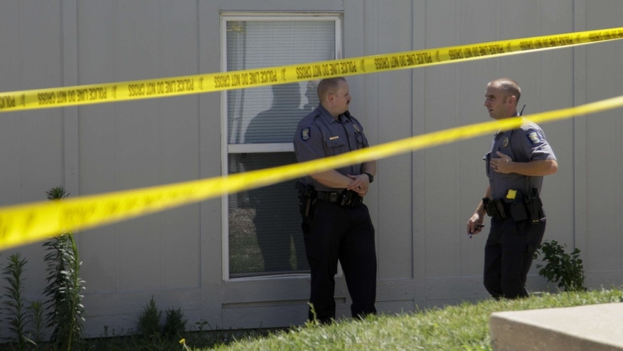 Lawrence Police attend the scene, Thursday, July 7, 2016,, near where an infant was found earlier in a Lawrence apartment complex's trash receptacle, police said.