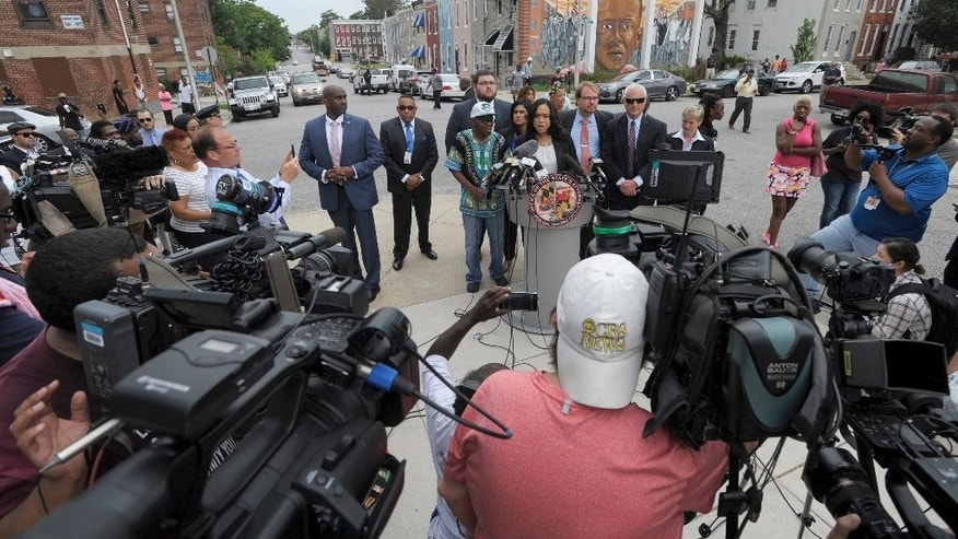 Baltimore State's Attorney Marilyn Mosby, at podium, holds a news conference near the site where Freddie Gray was arrested after her office dropped the remaining charges against three Baltimore police officers awaiting trial in Gray's death, in Baltimore, Wednesday, July 27, 2016. The decision by prosecutors comes after a judge had already acquitted three of the six officers charged in the case. At left is Gray's father, Richard Shipley. (AP Photo/Steve Ruark)