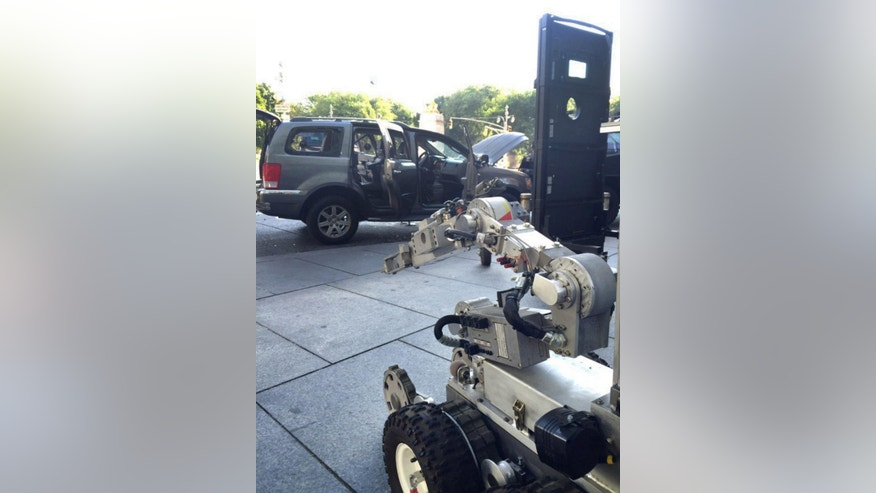 FILE- In this July 21, 2016 file photo provided by the New York Police Department, a police robot sits next to a suspect's vehicle following a standoff at Columbus Circle in New York. The driver, Hector Meneses, who is accused of throwing a fake bomb into a police van in Times Square that resulted in the standoff, has been ordered by a New York City judge to undergo psychiatric examination to determine whether he's fit to stand trial. A Manhattan judge ordered the exam Wednesday, July 27. (New York Police Department via AP )