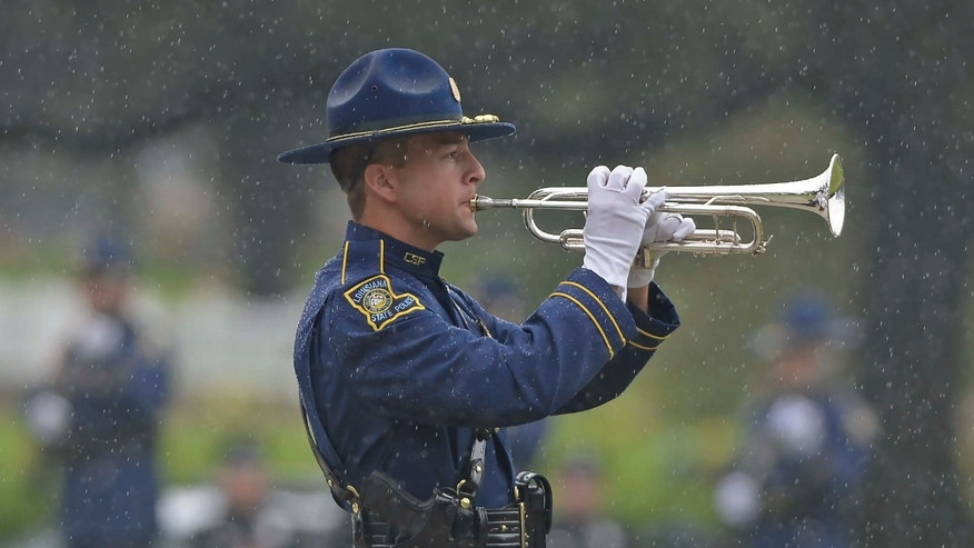 "July 25, 2016: A member of the Louisiana State Police Honor Guard plays ""Taps"" through driving rain during funeral services for Baton Rouge police Cpl. Montrell Jackson in Baton Rouge, La."
