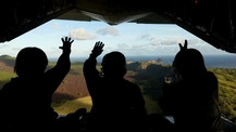 FILE - In this Dec. 9, 2015 file photo provided by the U.S. Air Force, Japan Air Self-Defense Force airmen wave at residents of Pagan island in the Commonwealth of the Northern Mariana Islands after dropping a package to the islanders as part of Operation Christmas Drop. Community members and an environmental group on Wednesday, July 27, 2016, sued the U.S. Navy, the Department of Defense and the secretary of defense over a plan to turn two Pacific islands, including Pagan, into live-fire testing sites.  (Staff Sgt. Benjamin Gonsier/U.S. Air Force via AP)