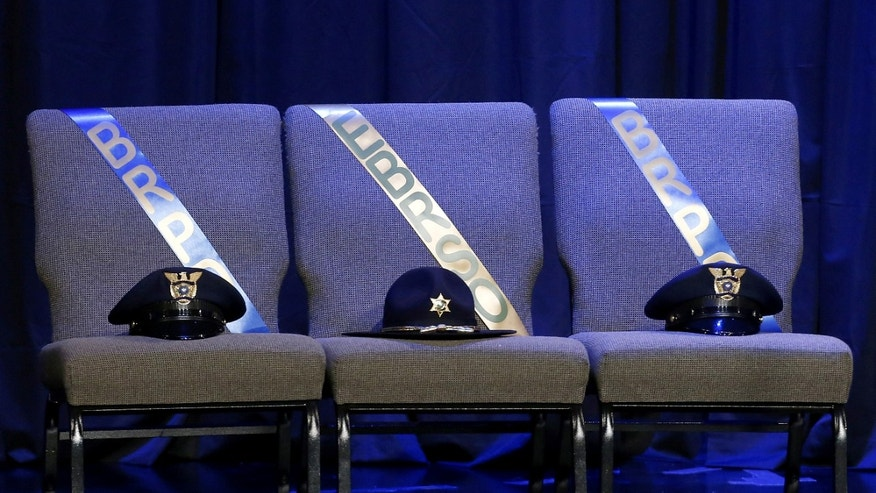 Three chairs honoring the slain Baton Rouge police officers are seen on stage at memorial service at Healing Place Church.