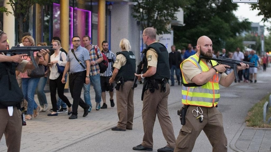 FILE - In this Friday, July 22, 2016 file photo, police escort people who leave the Olympia mall after shots were fired in Munich, southern Germany. The relentless series of mass killings across the globe poses a challenge for experts trying to analyze them without lapsing into faulty generalizations. Terms like contagion and copycat killing apply in some cases, not in others, they say, and in certain instances perpetrators' terrorist ideology intersects with psychological instability. (AP Photo/Sebastian Widmann, File)