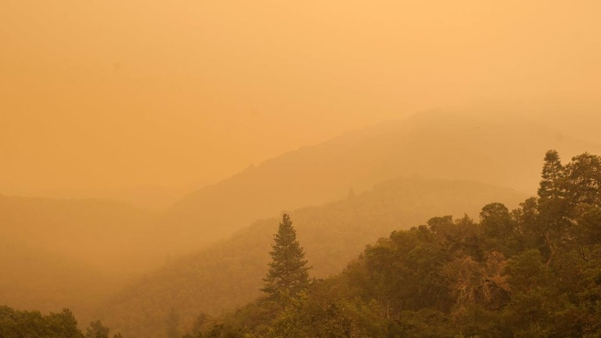 Smoke from a wildfire spreads over woods in Carmel Valley.