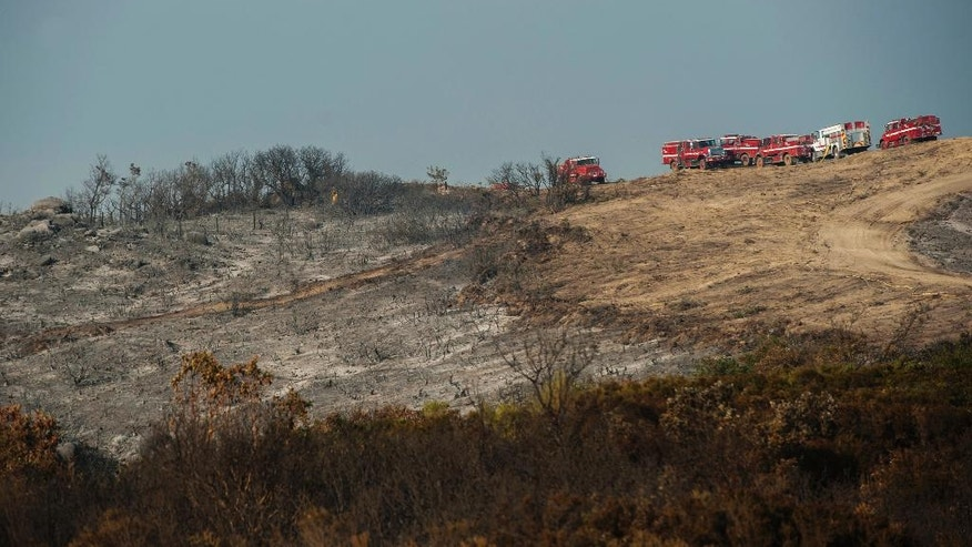 A firefighter, center left in yellow, walks on an area damaged by a wildfire near Carmel Highlands, south of Monterey, Calif., Wednesday, July 27, 2016. Acting Gov. Tom Torlakson, substituting for Gov. Jerry Brown who is at the Democratic National Convention with other top state officials, declared a state of emergency for the fire and another wildfire outside of Los Angeles on Tuesday night. The move frees up funding and relaxes regulations to help with the firefight and recovery. (AP Photo/Nic Coury)
