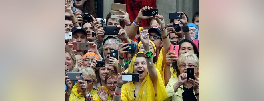 Faithful cheer and take pictures and videos with their phones of Pope Francis arriving by tram in Krakow's Jordan Park, Poland, Thursday, July 28, 2016. The Pope is on a five-day visit to Poland which will culminate with the World Youth Day on Sunday. (AP Photo/Gregorio Borgia)