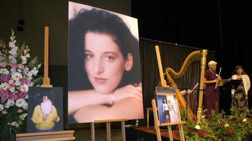 """FILE - In this May 28, 2002 pool-file photo taken at the Modesto Centre Plaza in Modesto, Calif., photos of Chandra Levy are on display as musicians, right, stand by at the memorial service for Levy. Prosecutors say they will not retry a man convicted of killing Washington intern Chandra Levy. The U.S. Attorney's office said in a statement Thursday, July 28, 2016, that the office has moved to dismiss the case charging Ingmar Guandique with Levy's 2001 murder. According to the statement, prosecutors concluded they could not convict Guandique """"based on recent unforeseen developments that were investigated over the past week."""" The statement does not elaborate. (AP Photo/Debbie Noda, Pool, File)"""