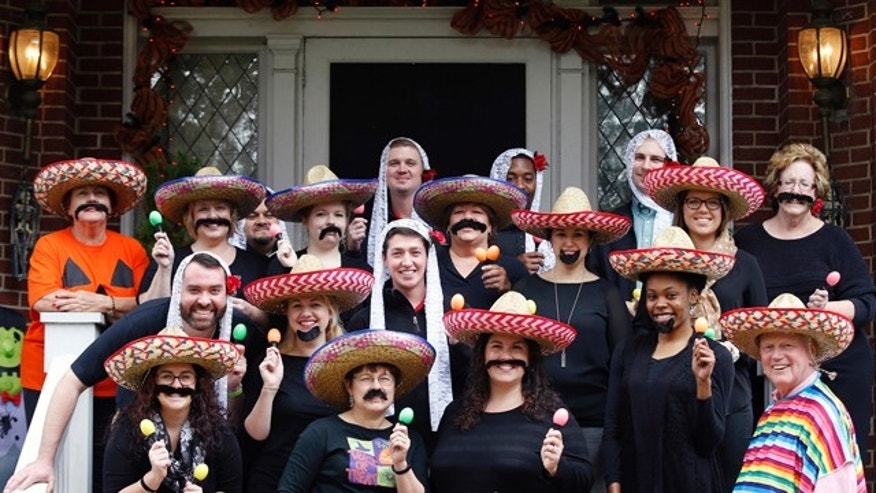 Oct. 28, 2015: University of Louisville President James Ramsey, lower right, and his wife, Jane, upper left, host a Halloween party. The University of Louisville has apologized after the photo surfaced showing Ramsey among staffers dressed in stereotypical Mexican costumes. (Scott Utterback/The Courier-Journal via AP)