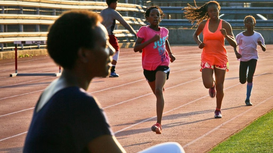"""In this Wednesday, July 20, 2016 photo, Tonia Handy, far left, sits near the track during an interview as her daughters Rainn Sheppard, 10, second from left, and Brooke Sheppard, 8, far right, run during track practice at Boys and Girls High School in the Brooklyn borough of New York. Rainn, Brooke and their older sister Tai, 11, live in a New York City homeless shelter with Handy, yet have earned top youth track rankings and a spot in this week's Junior Olympics. """"I want their dreams to come true. And I want them to be a part of it in making it happen,"""" said Handy. """"And hard work is something they are learning right here everyday on the track."""" (AP Photo/Bebeto Matthews)"""