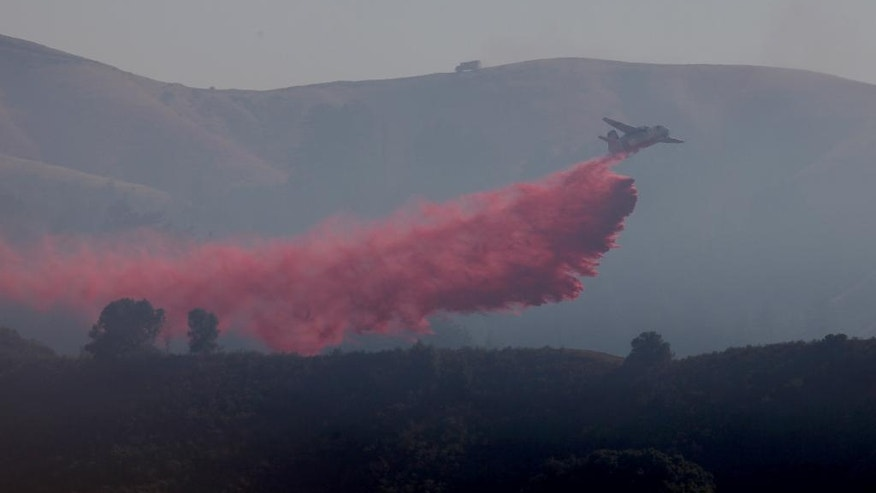 A plane drops fire retardant on a wildfire in Carmel Valley, Calif., Thursday, July 28, 2016. Firefighters struggled Thursday to get the upper hand on a massive wildfire burning along California's picturesque Big Sur coastline, where anxious residents driven from their homes awaited word on their properties and popular parks and trails closed at the height of tourist season. (Nic Coury/Monterey County Weekly via AP)