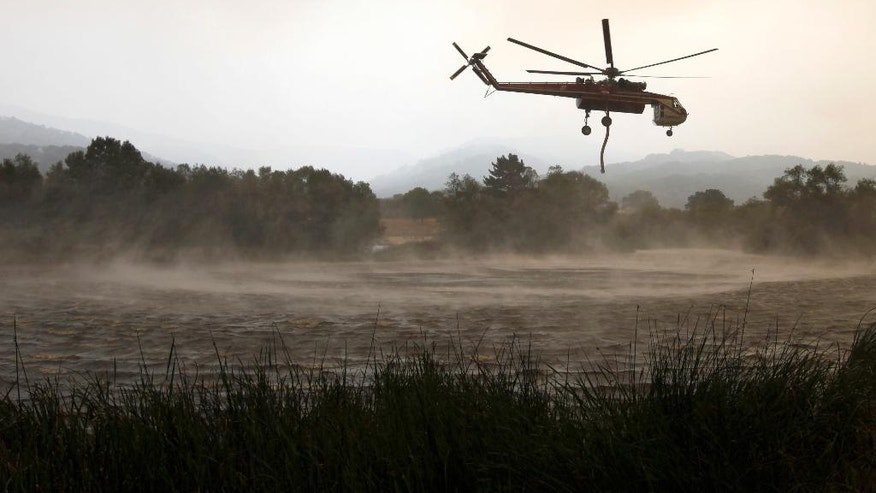 A helicopter picks up water near Robinson Canyon Road in Carmel Valley, Calif., to drop on the wildfire Thursday, July 28, 2016. Firefighters struggled Thursday to get the upper hand on a massive wildfire burning along California's picturesque Big Sur coastline, where anxious residents driven from their homes awaited word on their properties and popular parks and trails closed at the height of tourist season. (Nic Coury/Monterey County Weekly via AP)