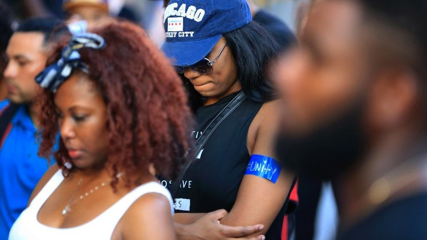 Protestors stop for a prayer during a march Friday, July 29, 2016, in Dallas. The event was organized by the same activist group that organized the July 7, protest that ended with the fatal shooting of multiple police officers. (AP Photo/Ron Jenkins)