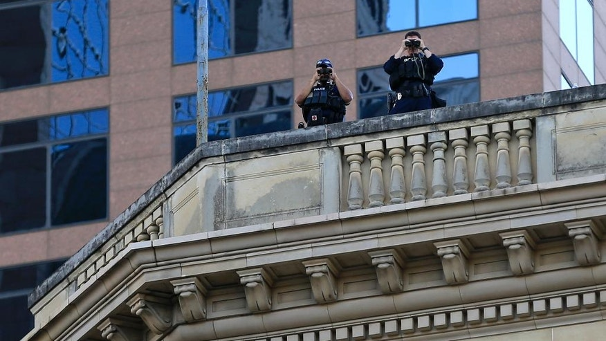 Police keep watch from above during a protest Friday, July 29, 2016, in Dallas. The event was organized by the same activist group that organized the July 7, protest that ended with the fatal shooting of multiple police officers. (AP Photo/Ron Jenkins)