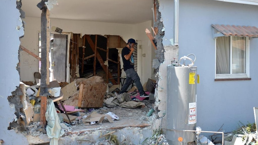 Relatives of the home owners sift through belongings Thursday, July 28, 2016, after a driver of a car plowed into the front of the Los Angeles house where a group of mostly elderly people were holding a bible study and prayer meeting, leaving one person dead and several injured. The vehicle left a gaping hole in the home and was almost entirely inside when it came to a rest late Wednesday.  (Brittany Murray/The Daily Breeze via AP)