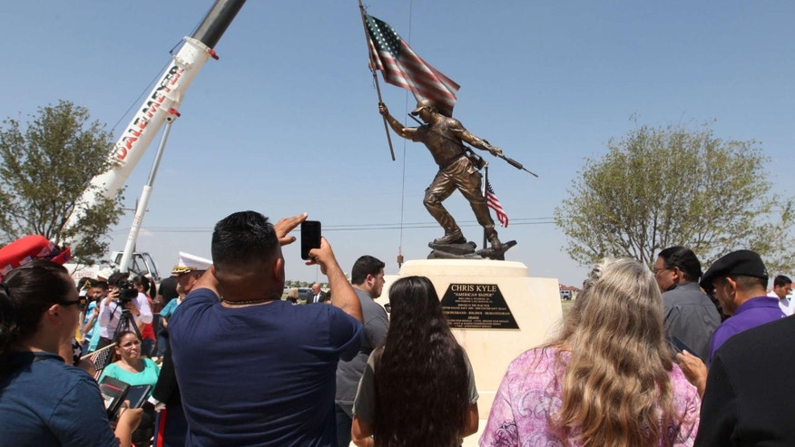 Supporters and spectators take photos of the Chris Kyle statue after the unveiling Thursday, July 28, 2016 at the Chris Kyle Memorial Plaza in Odessa, Texas.