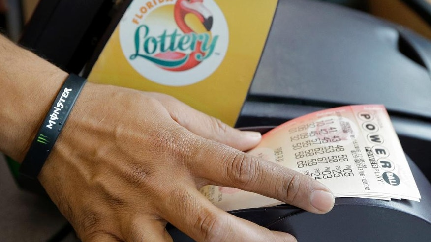 FILE - In this Jan. 13, 2016 file photo, a clerk at a convenience store pulls Powerball tickets from a printer for a customer in Tampa, Fla. The Powerball jackpot for the Wednesday, July 27, 2016, drawing has soared to over $420 million thanks to nearly three months without a winner of the big prize. (AP Photo/Chris O'Meara, File)