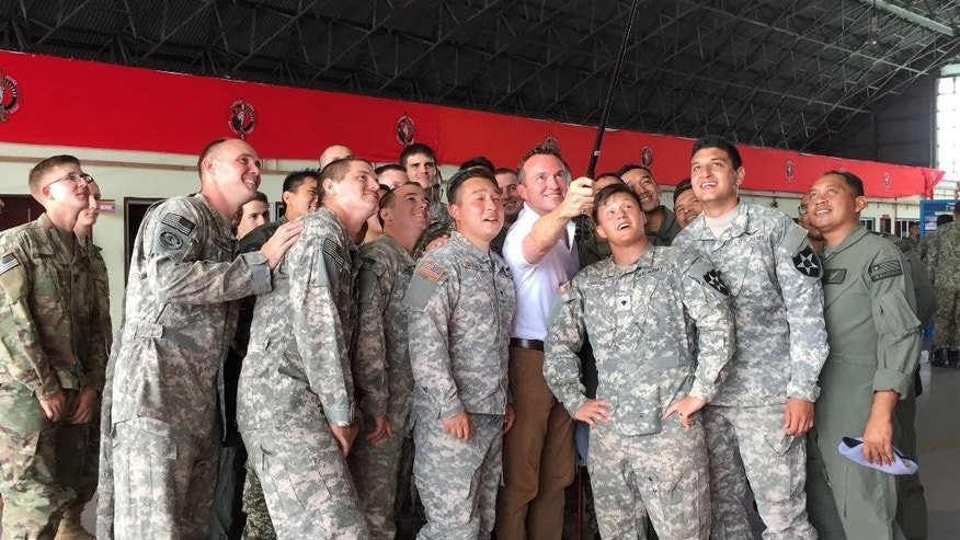 "U.S Army Secretary Eric Fanning, fourth from right, takes a selfie with fellow personnel during an annual joint military exercise with the Malaysian army in Johore Bahru, Malaysia, Saturday, July 30, 2016. Fanning says annual war games between the United States and South Korea will go ahead next month, despite North Korea's warning of a ""vicious"" showdown if the military drills proceed. (AP Photo/Eileen Ng)"