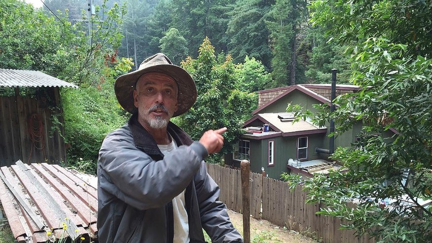 Resident Keith Bispo points to his house in the Palo Colorado community while interviewed in Big Sur, Calif., Friday, July 29, 2016. Bispo stayed at his house the past week to protect he and his neighbors' properties after the area was evacuated. Lodge managers and cafe owners along California's dramatic Big Sur coast were looking Friday at a summer of jittery guests and cancelled bookings after fire officials warned that crews will likely be battling a wildfire raging in steep, forested ridges just to the north for another month. (AP Photo/Terry Chea)