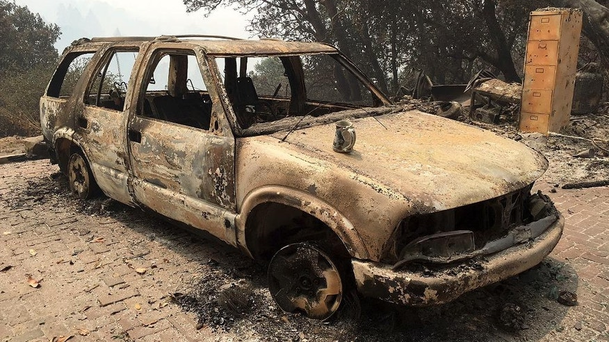 A car destroyed from wildfires sits in Big Sur, Calif., Friday, July 29, 2016. Lodge managers and cafe owners along California's dramatic Big Sur coast were looking Friday at a summer of jittery guests and cancelled bookings after fire officials warned that crews will likely be battling a wildfire raging in steep, forested ridges just to the north for another month. (AP Photo/Terry Chea)