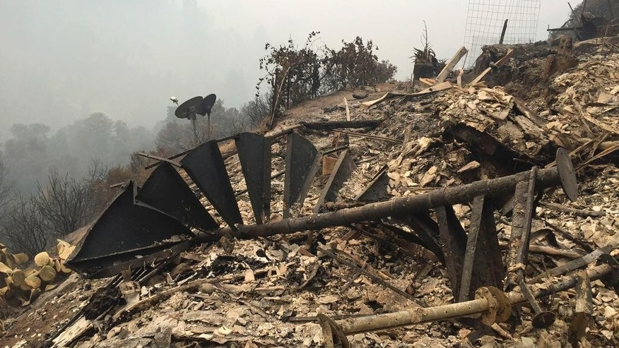 The remains of a staircase destroyed at a hilltop home is viewed in Big Sur, Calif., Friday, July 29, 2016. Lodge managers and cafe owners along California's dramatic Big Sur coast were looking Friday at a summer of jittery guests and cancelled bookings after fire officials warned that crews will likely be battling a wildfire raging in steep, forested ridges just to the north for another month. (AP Photo/Terry Chea)