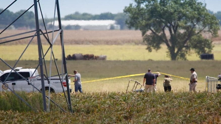 "Investigators surround the scene in a field near Lockhart, Texas where a hot air balloon carrying at least 16 people collided with power lines Saturday, July 30, 2016,  causing what authorities described as a ""significant loss of life.""  (Ralph Barrera/Austin American-Statesman via AP)"