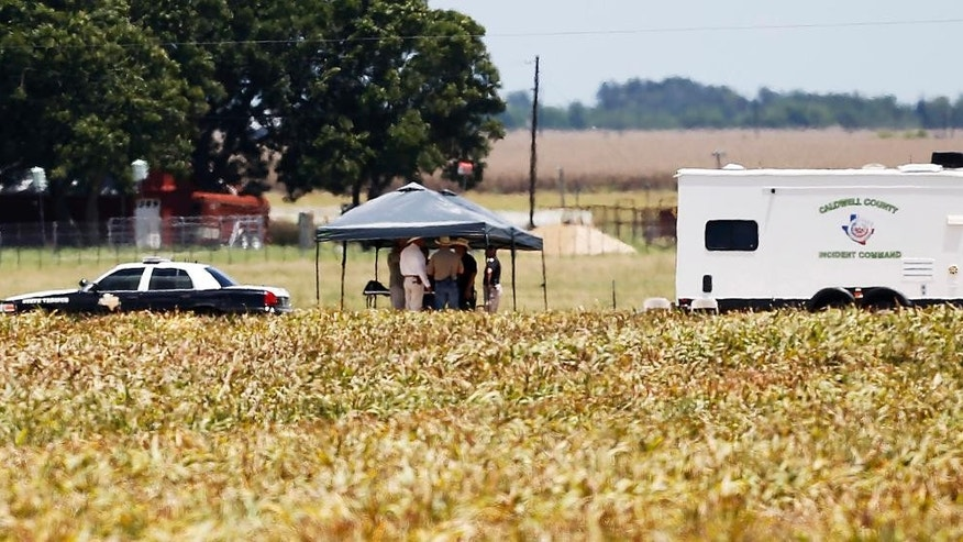 First responders and investigators appear at a scene of a balloon crash that reports indicate took the lives of several people in Central Texas near Lockhart, Texas, Saturday, July 30, 2016. (Kin Man Hui/The San Antonio Express-News via AP)