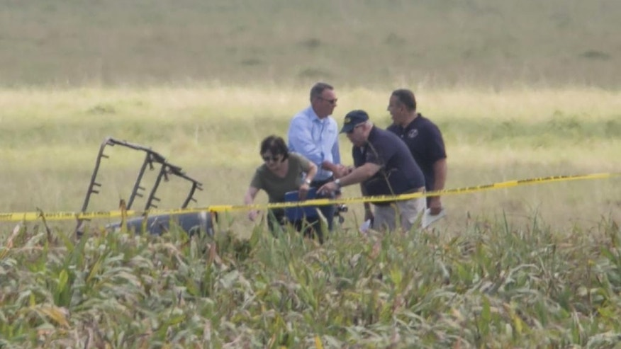"The partial frame of a hot air balloon is visible above a crop field as investigators comb the wreckage of a crash Saturday, July 30, 2016, in Central Texas near Lockhart, Texas. Authorities say the accident caused a ""significant loss of life."" (Ralph Barrera/Austin American-Statesman via AP)"