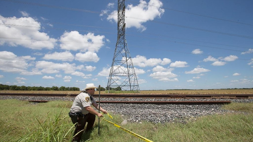 "Caldwell County Sheriff's Deputy Sean Quinn rolls out crime scene tape to secure the area where a hot air balloon carrying at least 16 people collided with power lines early Saturday, July 30, 2016, near Lockhart, Texas, causing what authorities described as a ""significant loss of life.""  (Ralph Barrera/Austin American-Statesman via AP)"