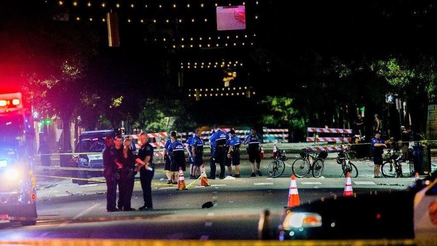 Police work the scene after gunshots rang out in downtown Austin, Texas, just as the bars were emptying early Sunday, July 31, 2016, leaving one woman dead and several others wounded, and police searching for a suspect.  (Ricardo B.Brazziell/Austin American-Statesman via AP)