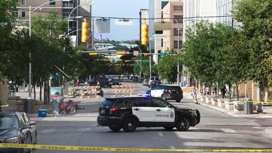 Police tape off areas on East 6th street in Austin, Texas, where a woman was fatally shot and several others wounded early Sunday, July 31, 2016. Police are still searching for the shooter, who opened fire in a crowded entertainment district in downtown Austin. (Jessalyn Tamez/Austin American-Statesman via AP)