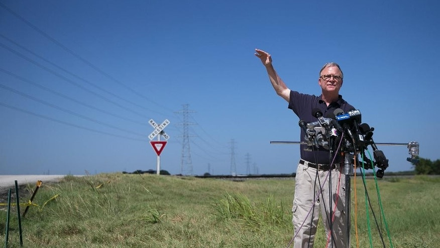National Transportation Safety Board (NTSB) member Robert Sumwalt talks about power lines, left, during a news conference at the scene of Saturday's hot air balloon crash near Lockhart, Texas, Monday, Aug. 1, 2016. The balloon made contact with the wires. Sixteen people were killed in the crash. (Deborah Cannon/Austin American-Statesman via AP)