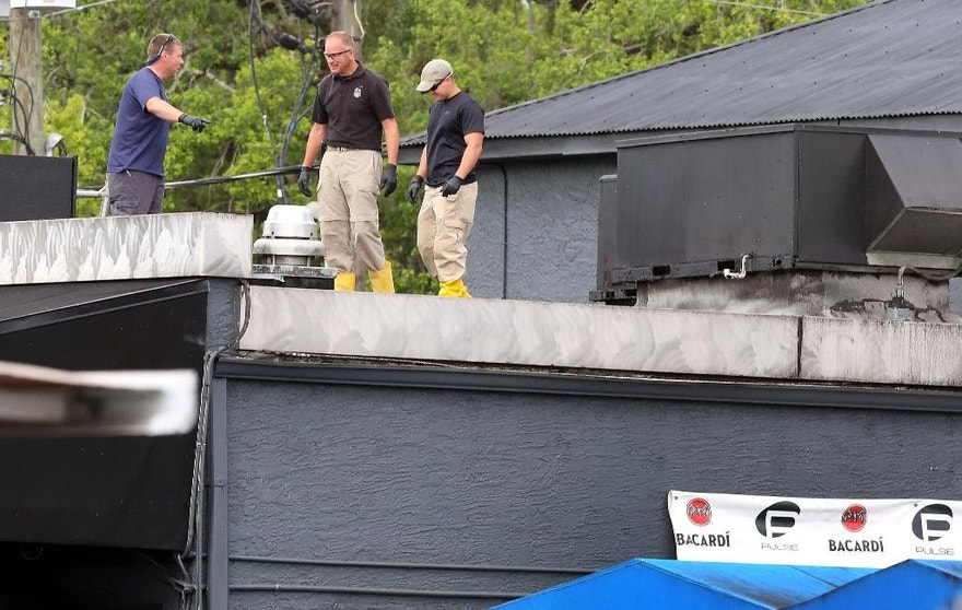 FBI  lab personnel walk on the roof of the Pulse Nightclub Monday, June 20, 2016, investigating the mass shooting scene in Orlando. Federal investigators promised to provide more insight as to what was happening inside the Pulse nightclub after a gunman started a deadly assault that was the worst mass shooting in modern U.S. history.  (Red Huber/Orlando Sentinel via AP)