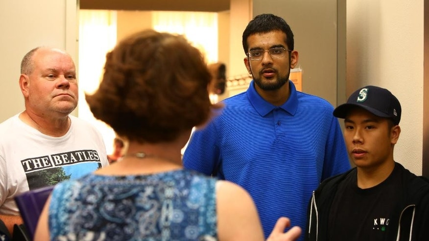 Court victims advocate Christina Harkness speaks with Mukilteo resident Terry Thomas, left, and friends of both the victims and suspect Sultan Akbar, second from right, and Andre Nguyen, right, after hearing for Allen Ivanov at Snohomish District Court in Everett, Wash., Monday, Aug. 1, 2016. A lawyer representing the 19-year-old accused of fatally shooting three other teens at a party in Washington state over the weekend says the case raises troubling questions about the availability of guns. (Genna Martin/seattlepi.com via AP)