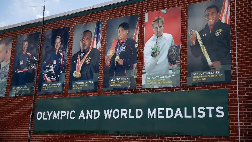 In this July 19, 2016 photo, photos celebrate past U.S. Army champion athletes, on the wall of the U.S. Army's World Class Athlete Program, at Fort Carson Army Base, outside Colorado Springs, Colo. U.S. Army Sgt. Hillary Bor and three other runners of Kenyan descent have taken a unique path to the Olympics through enlisting in the Army, earning U.S. citizenship, training with the military branch's World Class Athlete Program and making Team USA.  (AP Photo/Brennan Linsley)