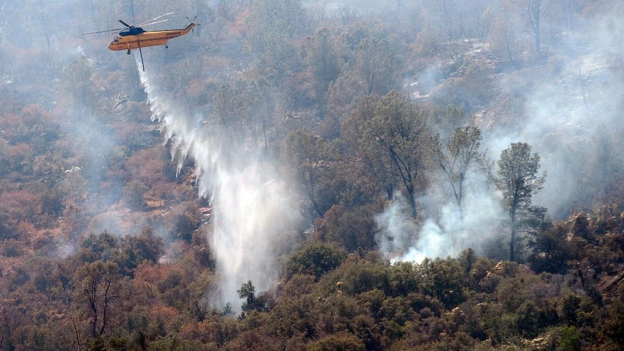 A work crew from the California Conservation Corps Butte County Fire Center cuts a line on Black Mountain near the town of Tollhouse, Calif., while fighting a blaze Monday, Aug. 1, 2016. (Craig Kohlruss/The Fresno Bee via AP)