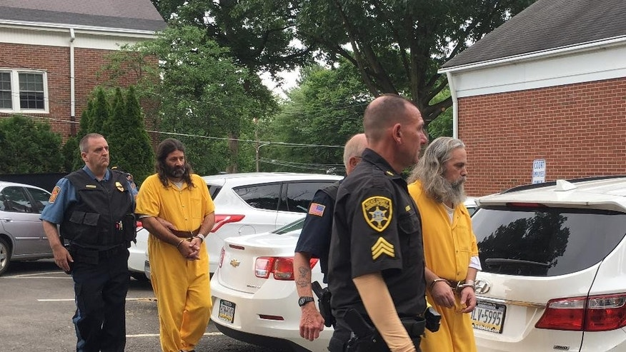 Daniel Stoltzfus, left in yellow, and Lee Kaplan, right in yellow, are led to a preliminary hearing Tuesday, Aug. 2, 2016, outside Bucks County Magisterial District Judge John I. Waltman's courtroom in Feasterville, Pa. Daniel Stoltzfus and his wife Savilla Stoltzfus were ordered to stand trial on charges they gave away their 14-year-old daughter to a Philadelphia-area man after he helped them out financially. Kaplan also was ordered to trial on sexual assault charges. (AP Photo/Megan Trimble)