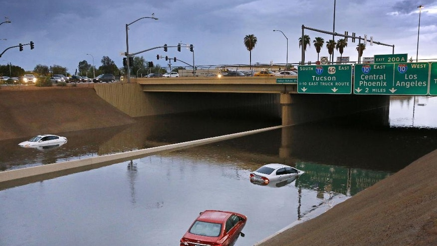 Cars sit stranded in flood waters along Interstate 17, Tuesday, Aug. 2, 2016 in Phoenix. wo high schools in southern Arizona were evacuated as a precaution Tuesday and some drivers had to be rescued as flooding closed several major roads and stranded motorists between flowing washes. (David Kadlubowski/The Arizona Republic via AP)
