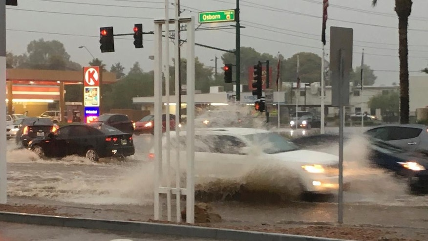 In this photo taken Tuesday, Aug. 2, 2016, cars make their way through a flooded intersection in Phoenix. The desert Southwest is poised to get a second soaking after monsoon rains hit the region, stranding drivers, flooding streets and prompting water rescues. The rains bring some relief to crews fighting wildfires, but also the potential for mudslides in areas blackened by flames. (AP Photo/Alan Clendenning)