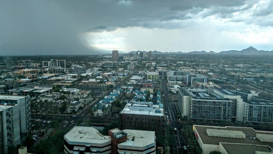 In this Tuesday, Aug. 2, 2016 photo provided by Brody McMahan, a storm is seen over downtown Phoenix. The desert Southwest is poised to get a second soaking after monsoon rains rollicked the region, stranding drivers, flooding streets and prompting water rescues. (Courtesy of Brody McMahan via AP)