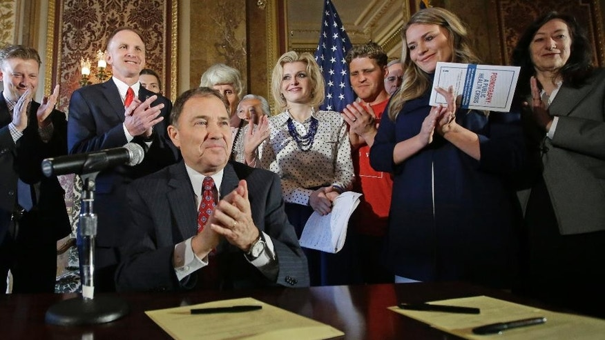 FILE--In this April 19, 2016, file photo, Utah Gov. Gary Herbert and supporters applaud during a ceremonial signing of a state resolution declaring pornography a public health crisis in Salt Lake City, Utah. Utah's declaration of pornography as a public health crisis has created a backlash from sexually explicit publications, earning Herbert a mention on the latest cover of Penthouse magazine, which also sent copies of the issue to him and leaders in the Utah-based Mormon church. (AP Photo/Rick Bowmer, file)