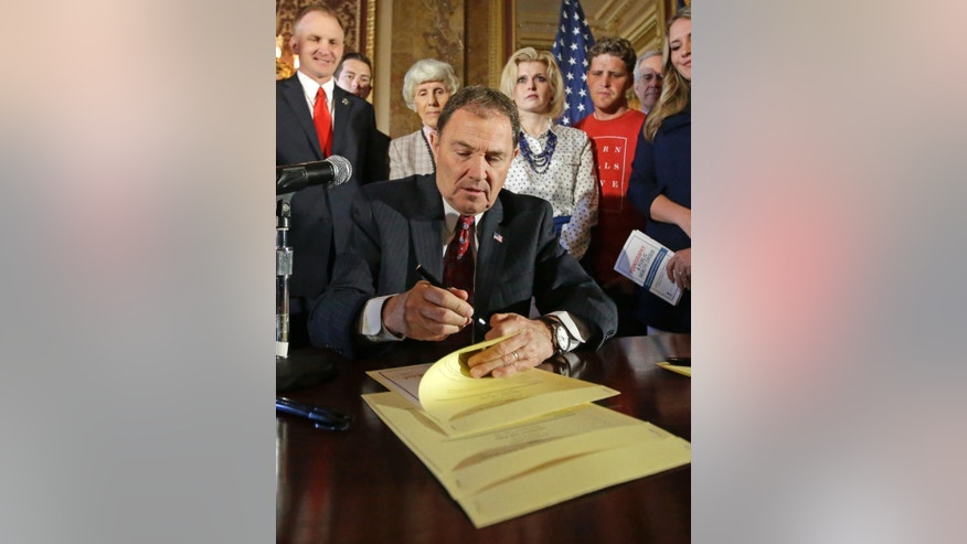 FILE- In this April 19, 2016, file photo, Utah Gov. Gary Herbert signs a state resolution declaring pornography a public health crisis in Salt Lake City. Utah's declaration of pornography as a public health crisis has created a backlash from sexually explicit publications, earning Herbert a mention on the latest cover of Penthouse magazine, which also sent copies of the issue to him and leaders in the Utah-based Mormon church. (AP Photo/Rick Bowmer, File)