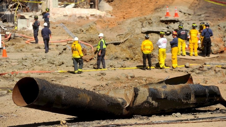 FILE - In this Sept. 11, 2010, file photo, a natural gas line lies broken on a San Bruno, Calif., road after a massive explosion. The blast of a Pacific Gas & Electric Co. natural gas pipeline sent a giant plume of fire into the air in a neighborhood in San Bruno, killing eight people and destroying 38 homes. The surprising decision by federal prosecutors in San Francisco to slash nearly all of a potential $562 million fine in a criminal case against one of the nation's largest utilities has raised concerns about the office's handling of corporate prosecutions in the wake of a criminal case against shipping giant FedEx that prosecutors abruptly abandoned recently during trial. (AP Photo/Noah Berger, File)