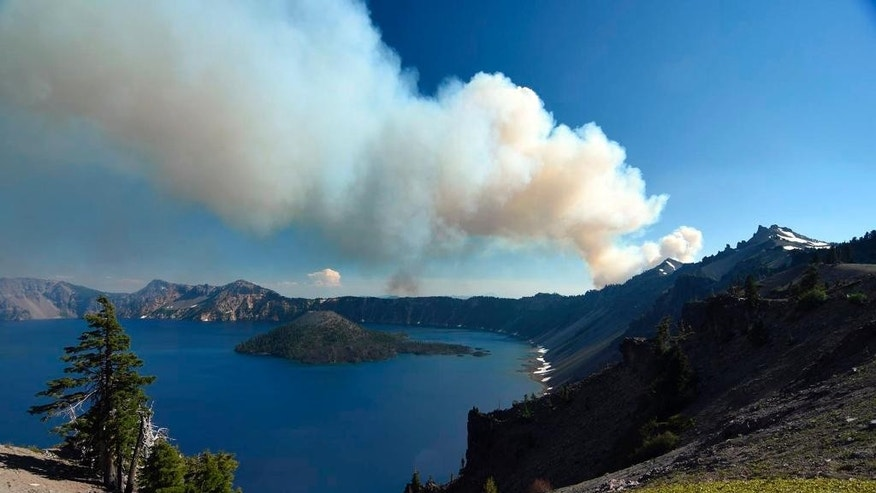 This photo provided by Inciweb.gov, shows smoke from Bybee Creek Wildfire drifting over Crater Lake, Ore., July 30, 2016. The wildfire burning west of Crater Lake National Park has grown to more than 400 acres as of Tuesday, and the park remains open, but fire officials say West Rim Drive could be intermittently closed over the next couple of days. (Cheryl Chipman/Inciweb.gov via AP)
