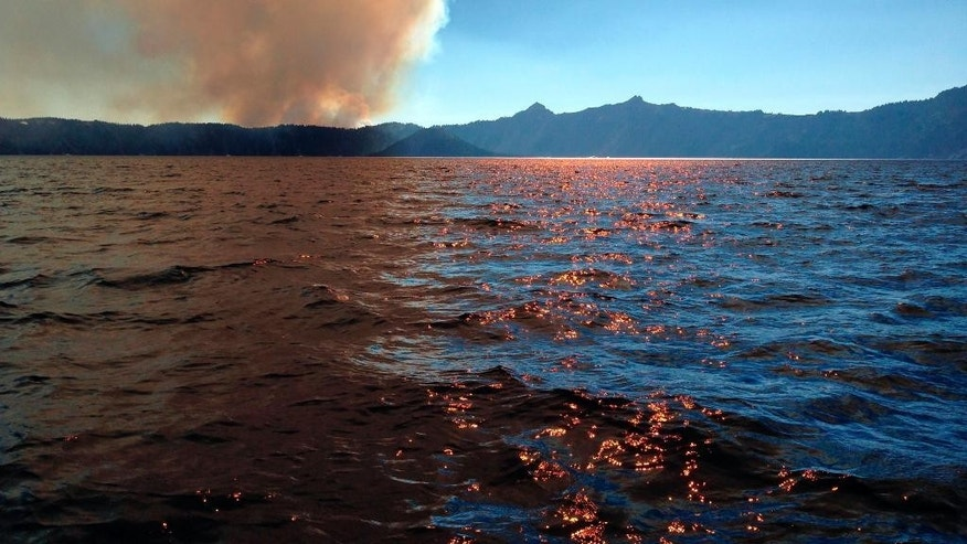 This photo provided by Inciweb.gov, shows smoke from Bybee Creek Wildfire drifting over Crater Lake, Ore., Monday Aug. 1, 2016. The wildfire burning west of Crater Lake National Park has grown to more than 400 acres as of Tuesday,  and the park remains open, but fire officials say West Rim Drive could be intermittently closed over the next couple of days. (Ashley Waymouth/Inciweb.gov via AP)