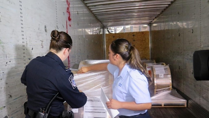 U.S. Customs and Border Protection officer Rachel McCormick, left, and Mexican customs officer Alejandra Galindo demonstrate how they would jointly inspect a cargo truck carrying goods from Mexico into the U.S. while at the Mariposa Inspection Facility at the Nogales Port of Entry in Arizona. Officials say the new program allowing Mexican officials to work with their U.S. counterparts has already reduced wait times by more than 75 percent. (AP Photo/Astrid Galv'n)