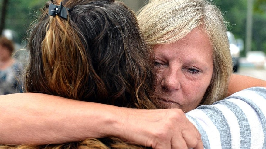 """Ginny Peak, right, sister of Garr Keith Hardin embraces a family member following court proceedings, Thursday, Aug. 4, 2016 at the Meade County Courthouse in Brandenburg Ky. A Kentucky judge is considering whether Garr Keith Hardin and Jeffrey Dewayne Clark should be let out of jail after spending more than 20 years in prison before their murder convictions in what prosecutors called a """"satanic"""" killing were vacated.  (AP Photo/Timothy D. Easley)"""