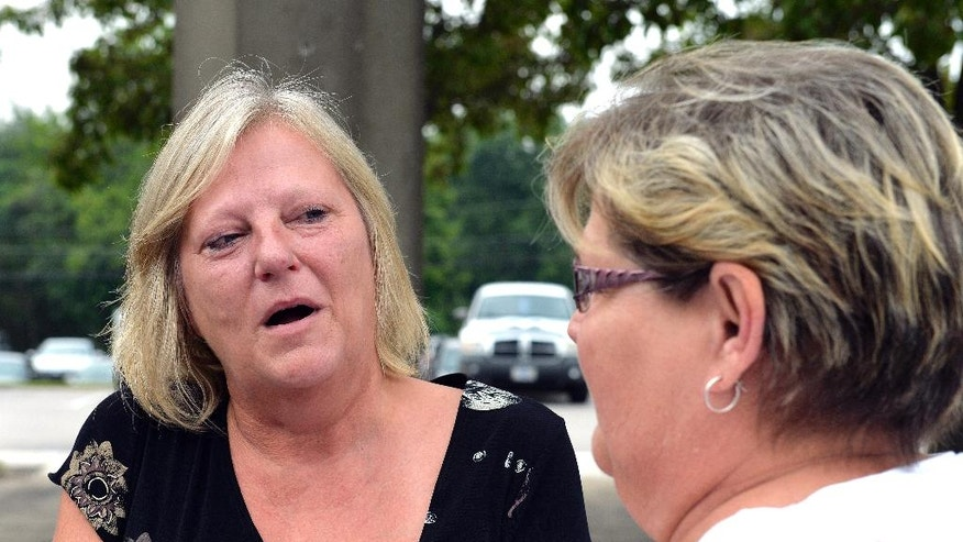 """Ginny Peak, left, sister of Garr Keith Hardin speaks with a family member following court proceedings, Thursday, Aug. 4, 2016 at the Meade County Courthouse in Brandenburg Ky.  A Kentucky judge is considering whether Garr Keith Hardin and Jeffrey Dewayne Clark should be let out of jail after spending more than 20 years in prison before their murder convictions in what prosecutors called a """"satanic"""" killing were vacated. (AP Photo/Timothy D. Easley)"""