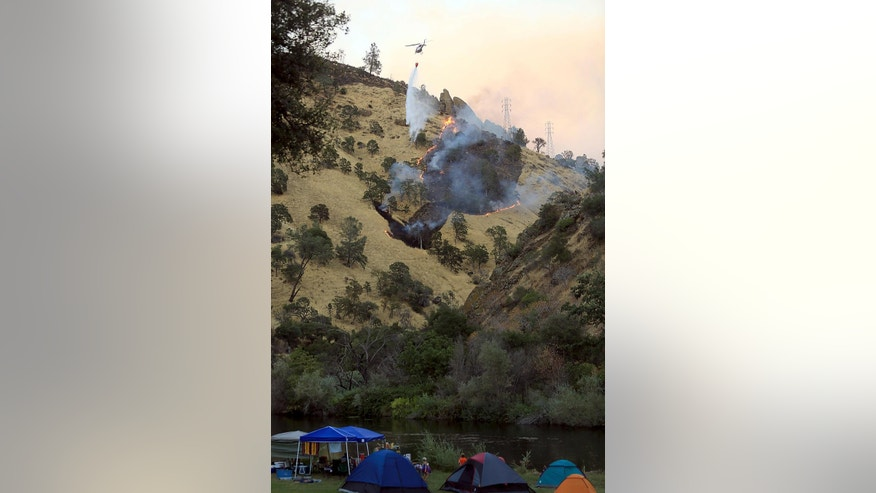 Campers watch as the Cold fire slopes down a ridge on Putah Creek in Lake Berryessa, Calif.